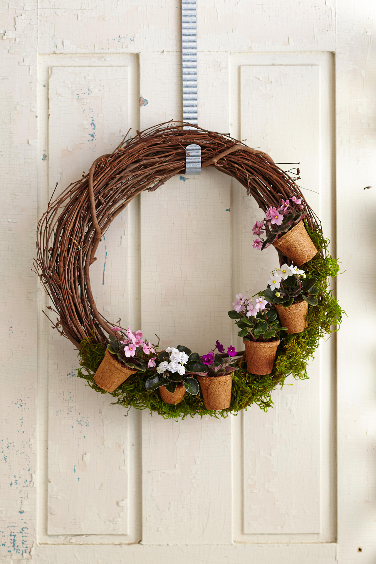 Flower pots on wreath made from twigs hanging on door