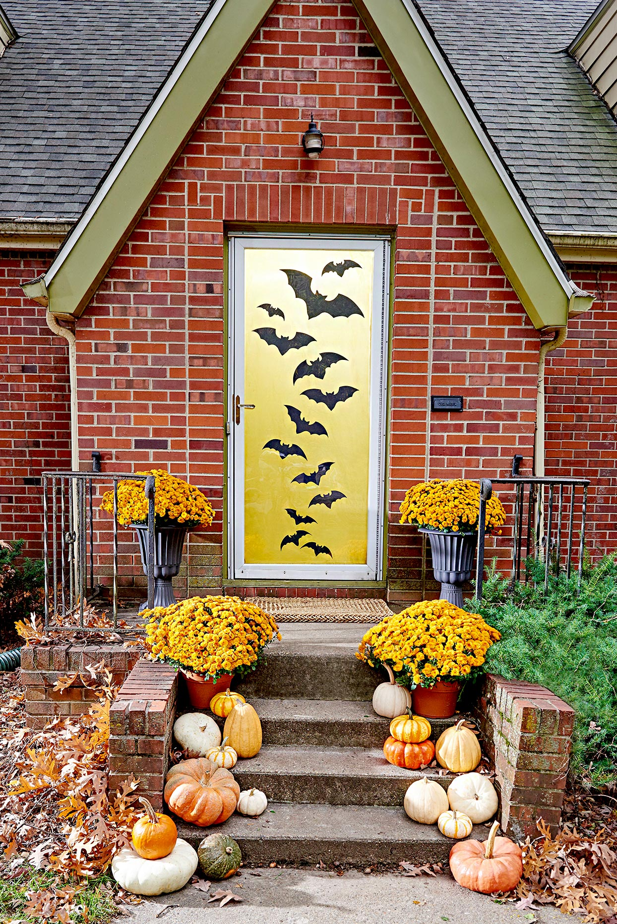 Front porch with bats on door, and pumpkins on stairs