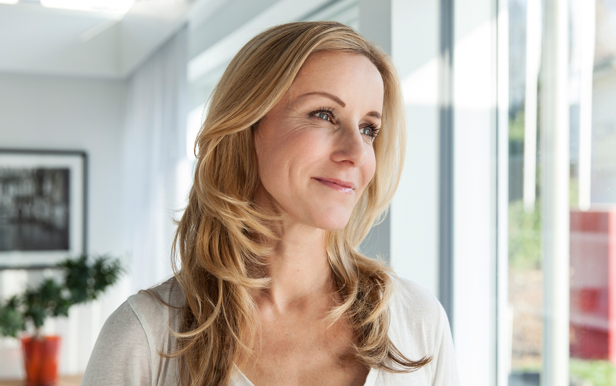 middle aged woman with long blonde hair staring outside