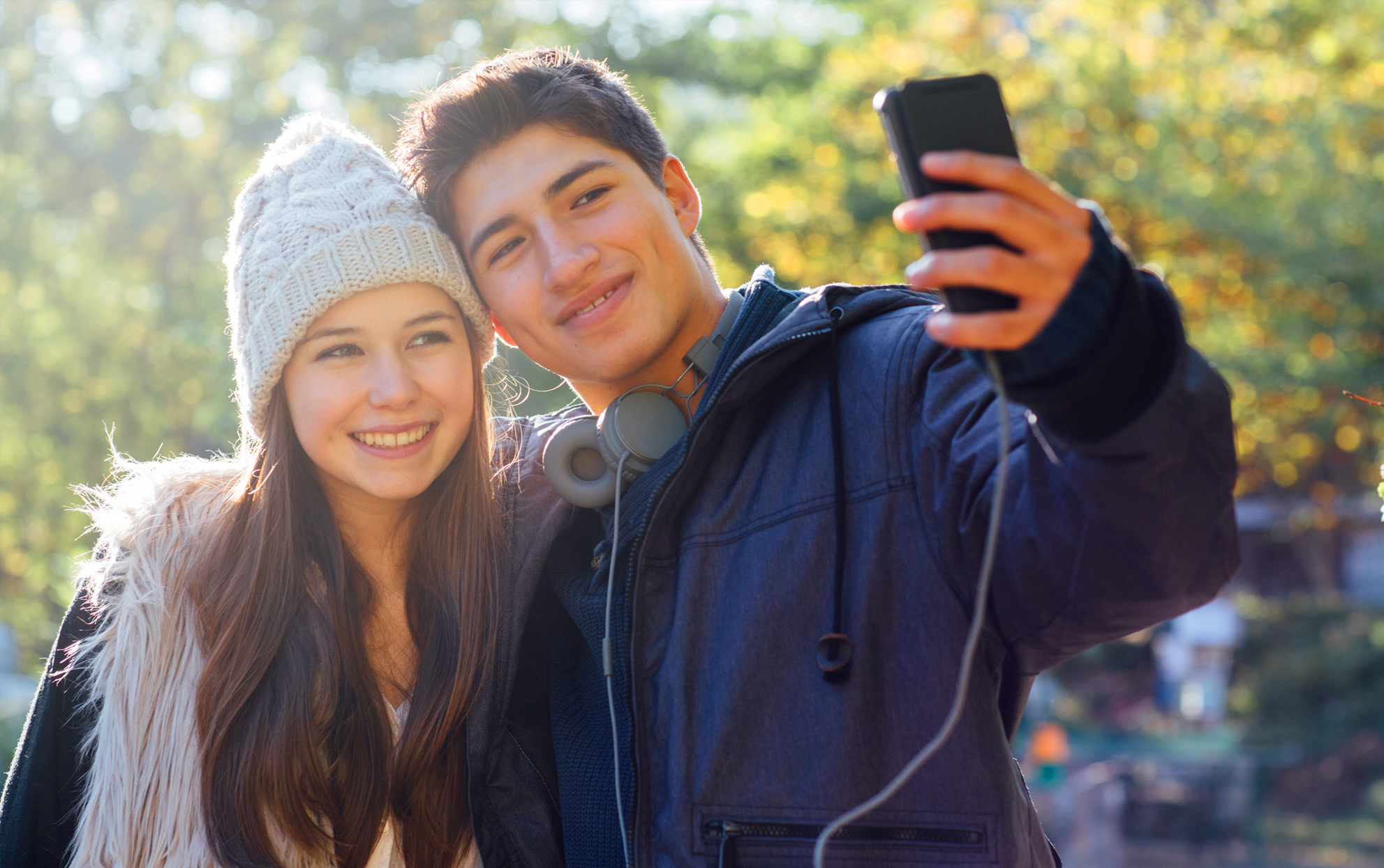 Male and female teen taking selfie outside
