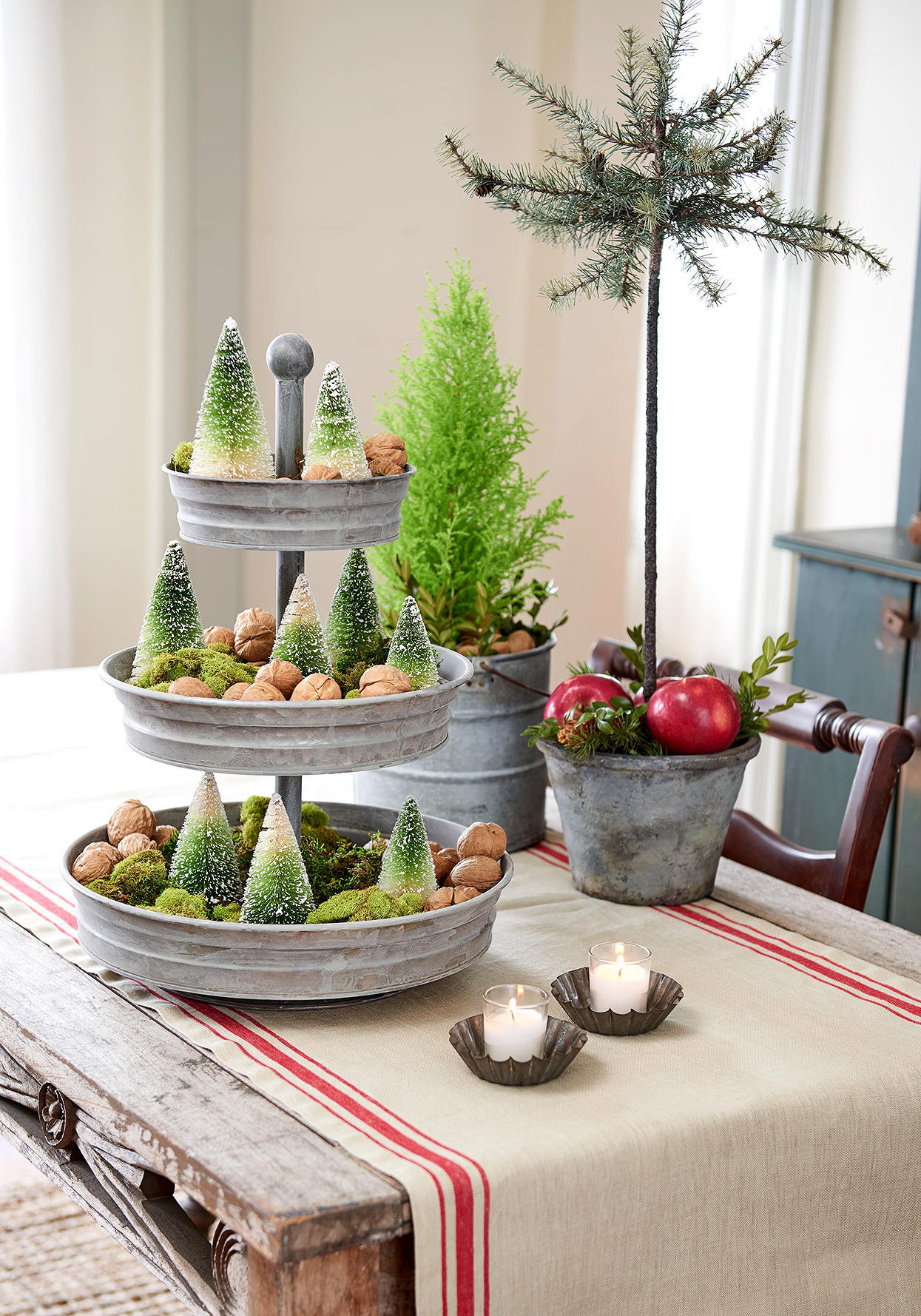 Christmas table centerpiece with trees and chestnuts on tiered tray
