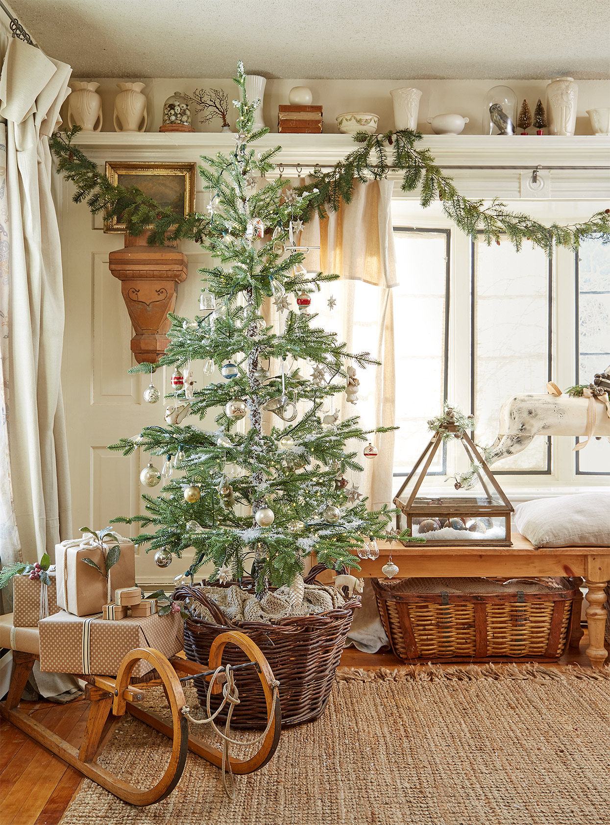 Christmas tree in basket near vintage sled in farmhouse room