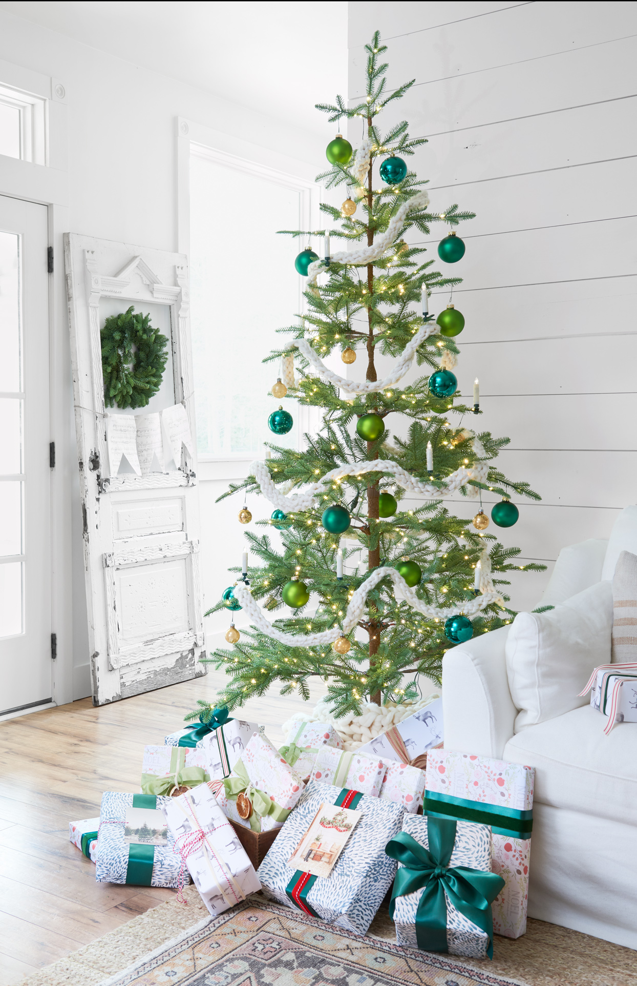 christmas tree decorated with green bulbs and presents with green ribbon