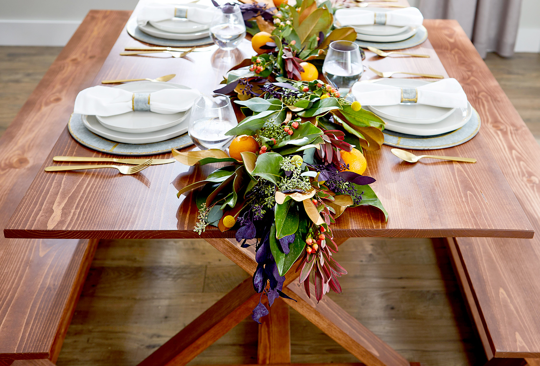 Dining table with runner made of plants and oranges