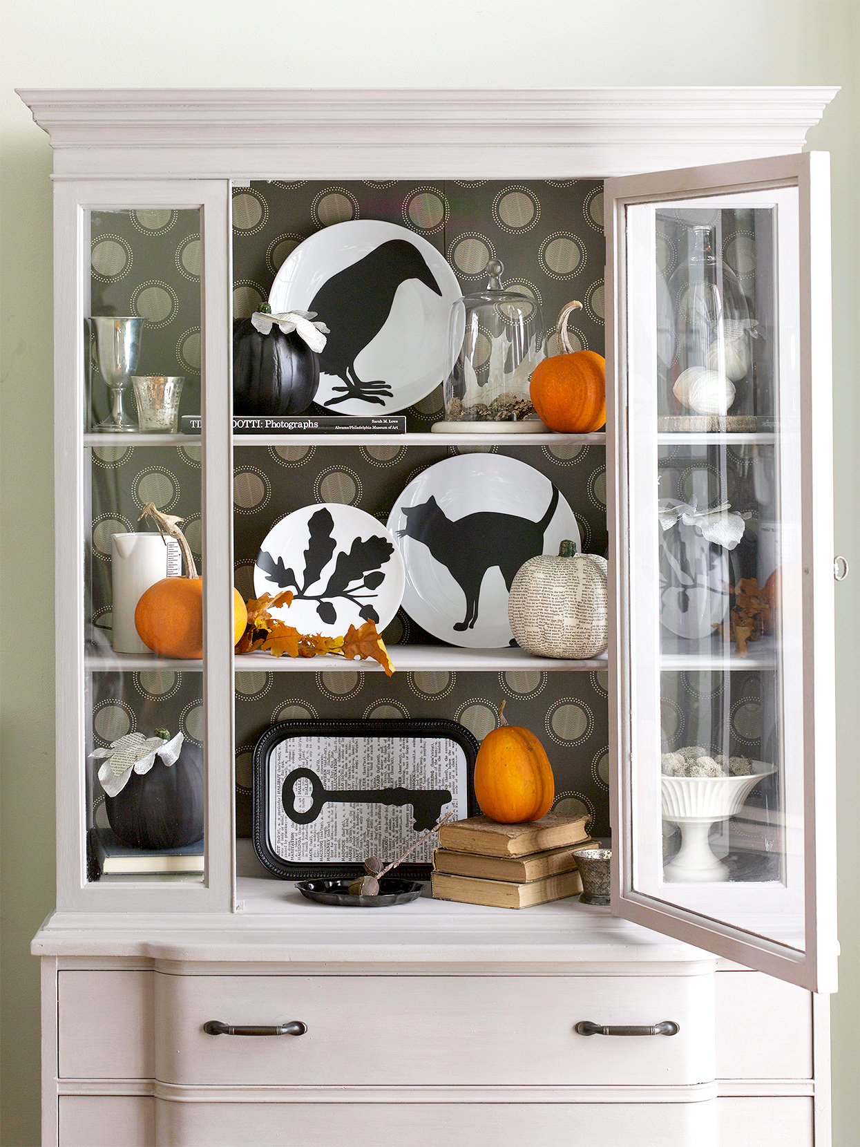 Halloween silhouettes adhered to plates in cabinet