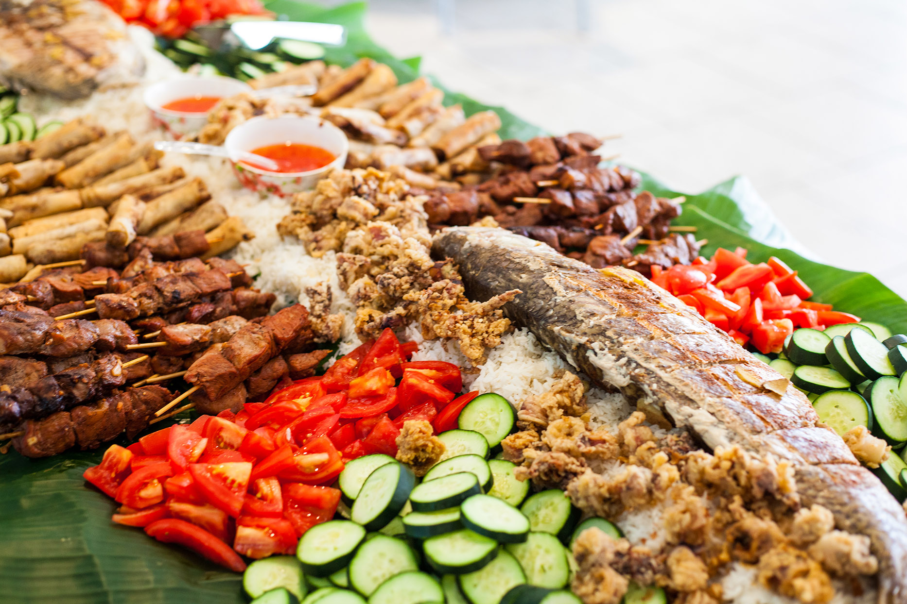 whole cooked fish on top of vegetables and meat