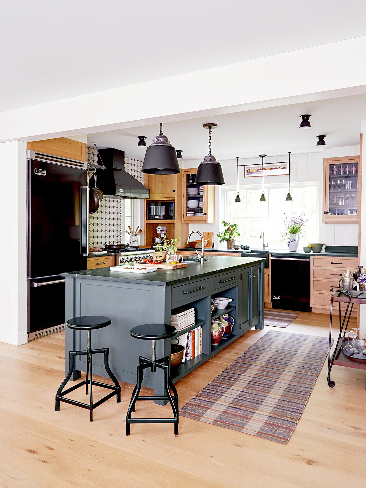 Kitchen with black island and stools