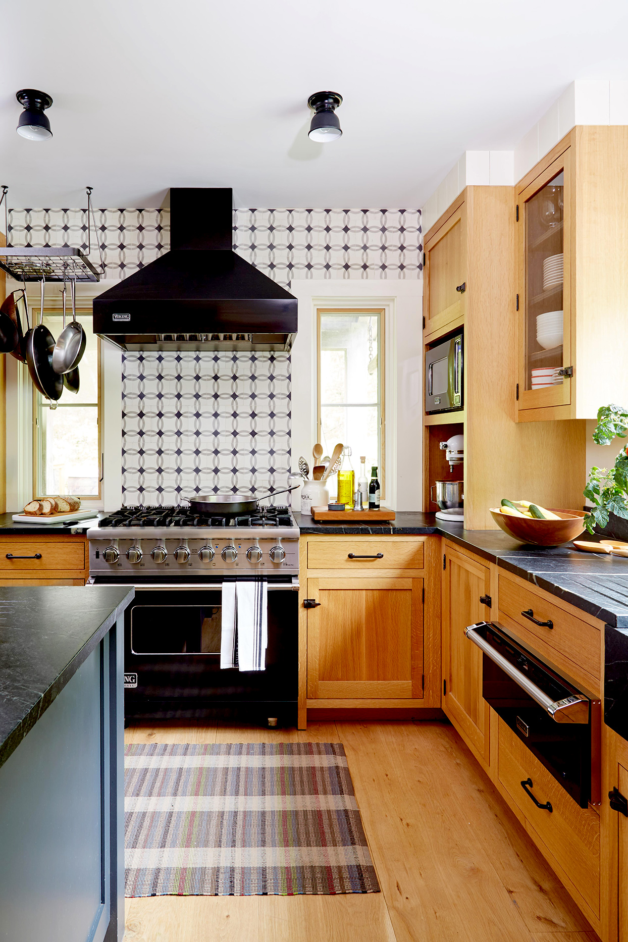 Kitchen with wooden cabinets and geometric wallpaper