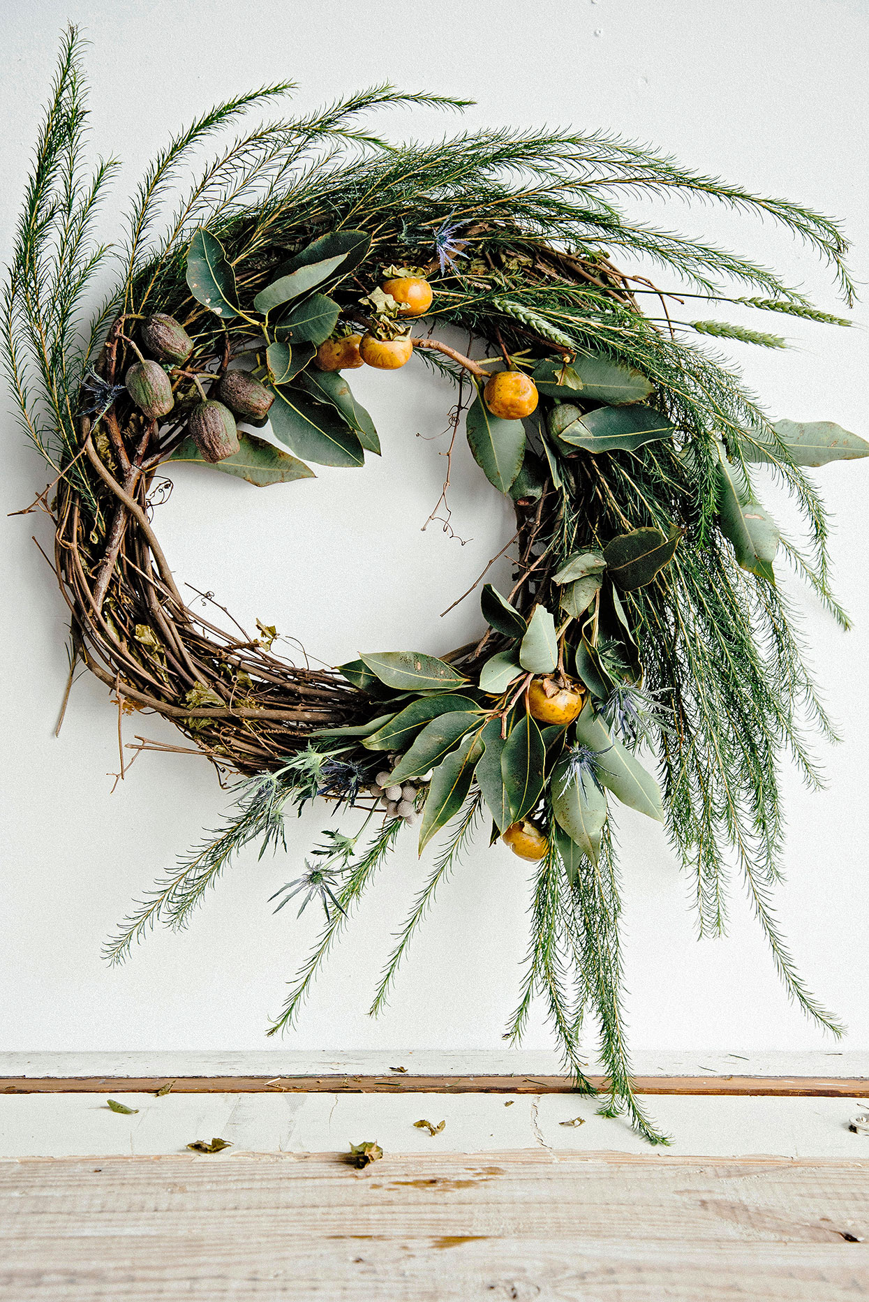 grapevine wreath base with persimmon, eucalyptus nuts and thistle