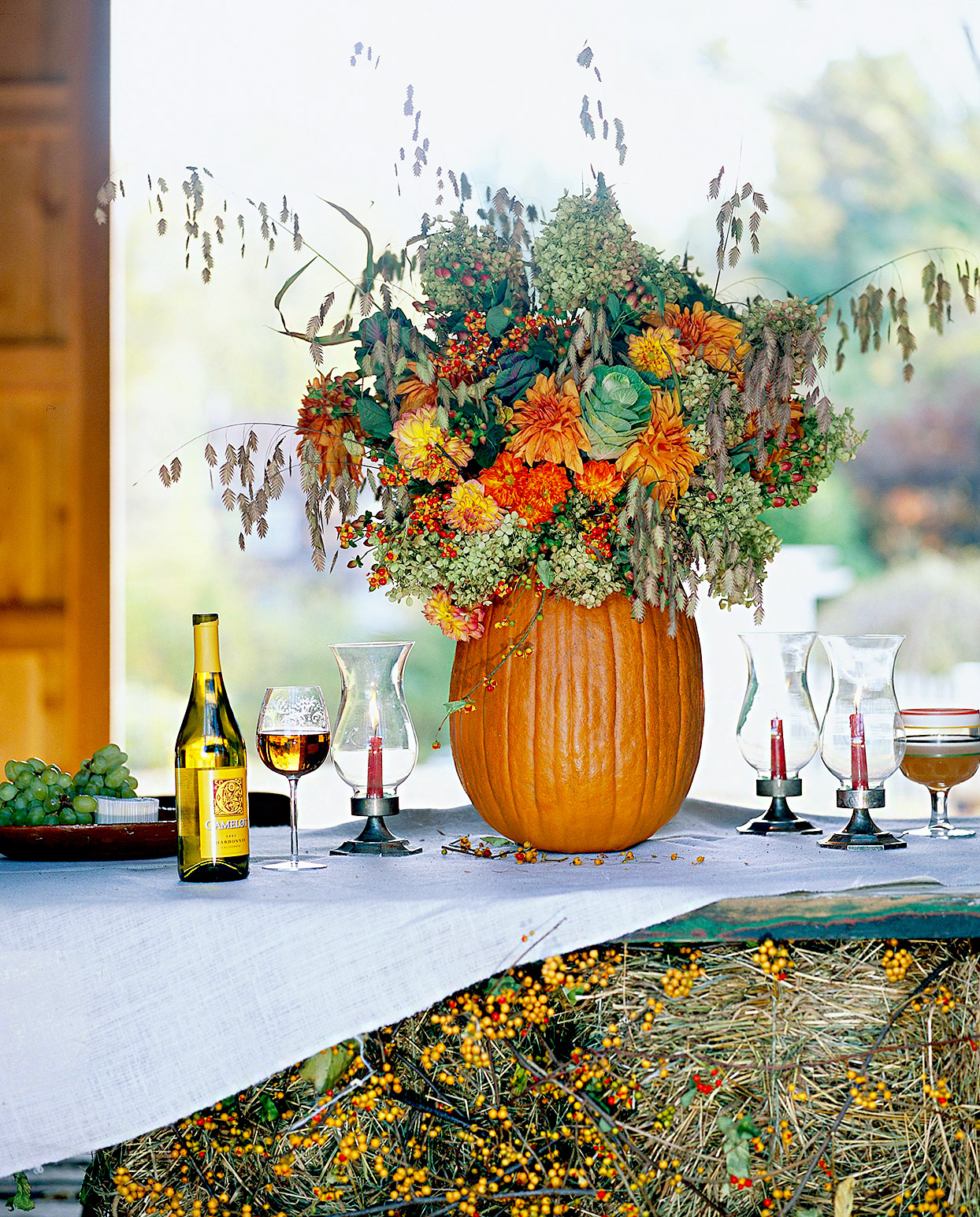 Pumpkin centerpiece with fall plants and table setting