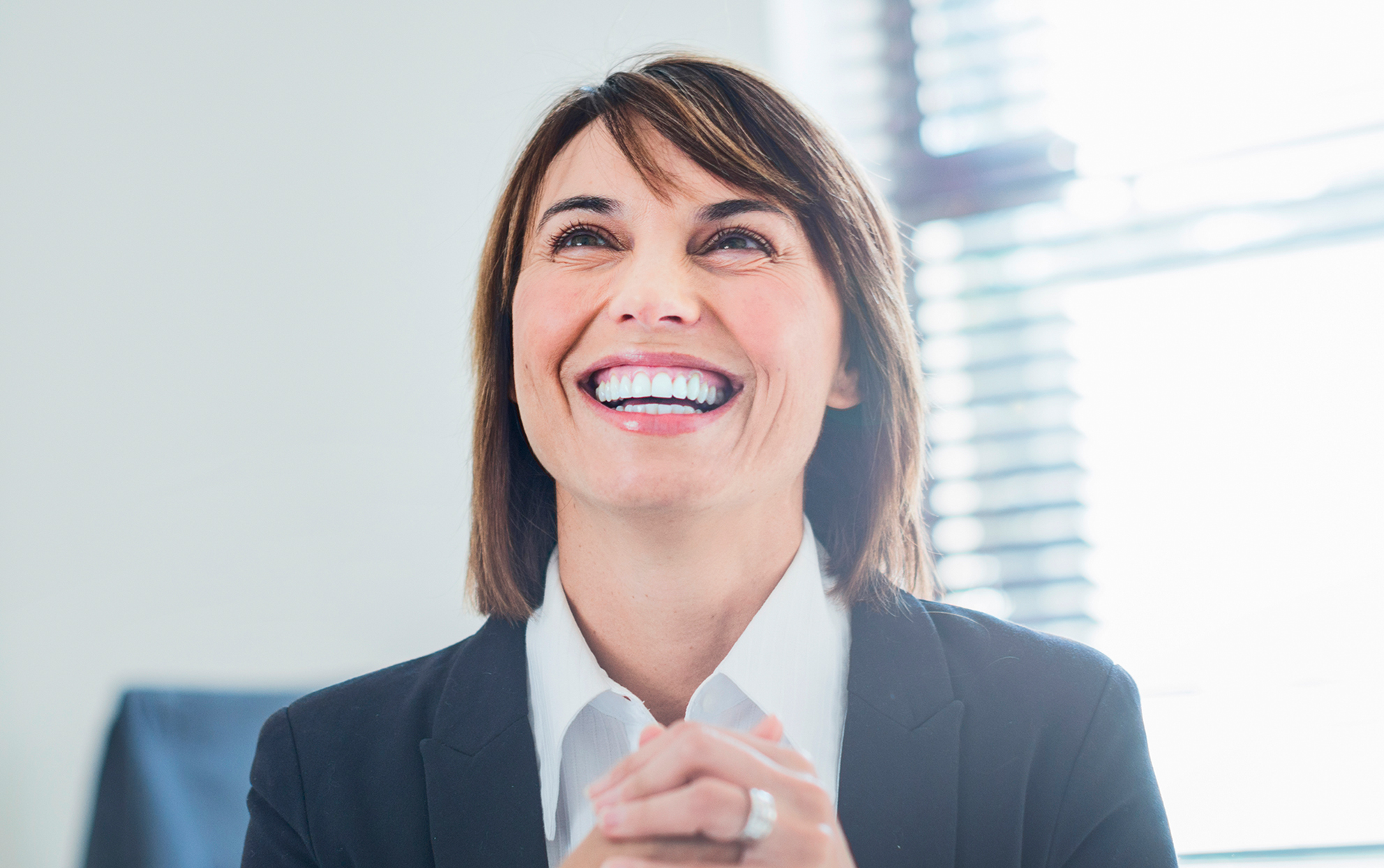 woman smiling in an office with short brown hair