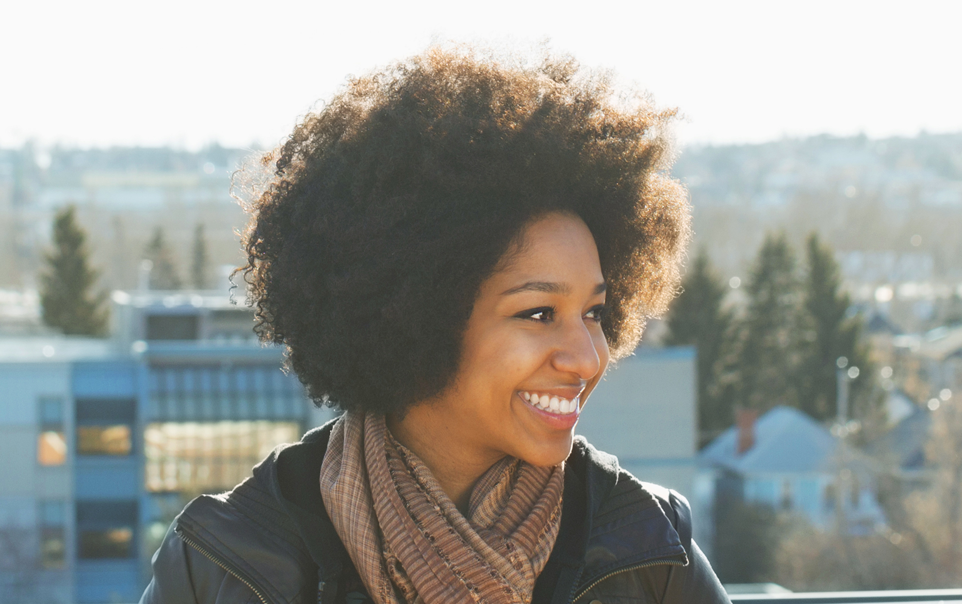 african american woman with short curly hair smiling outside in a jacket