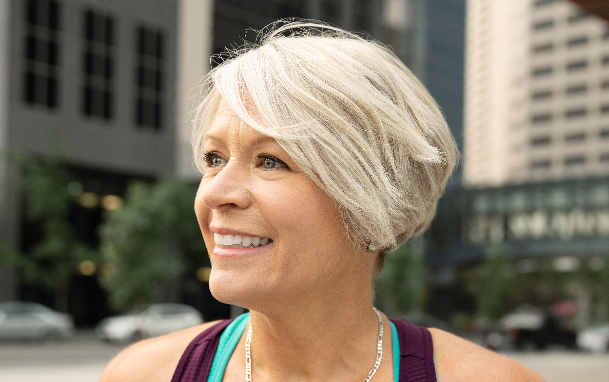 older woman with silver blonde short hair smiling outside