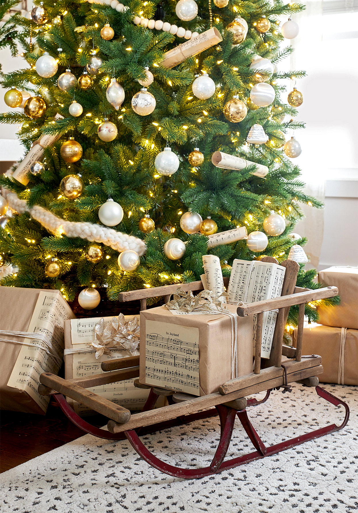vintage sled with music-inspired gift wrap near tree