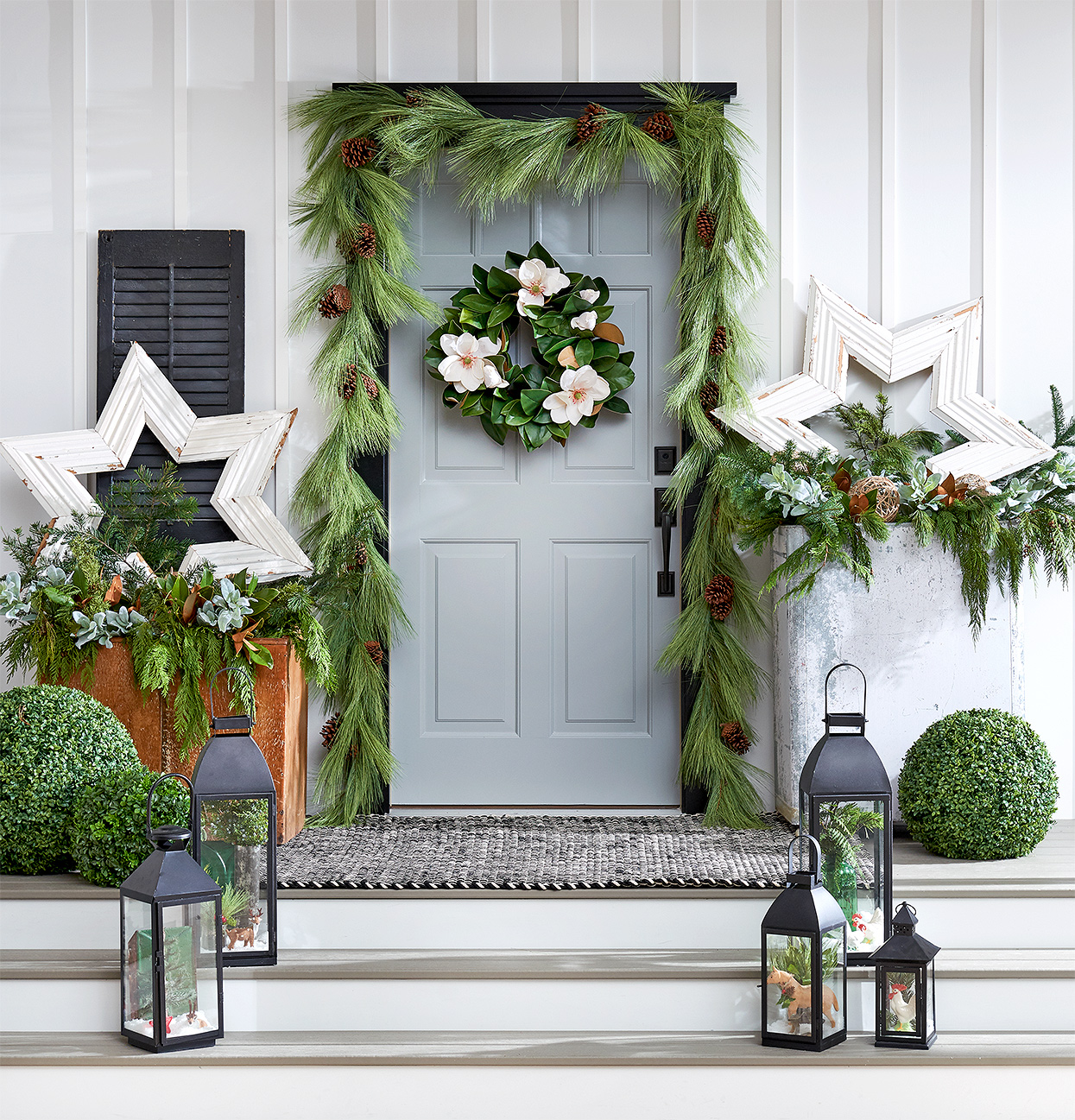 Christmas decorated porch with star decor, garland and lanterns