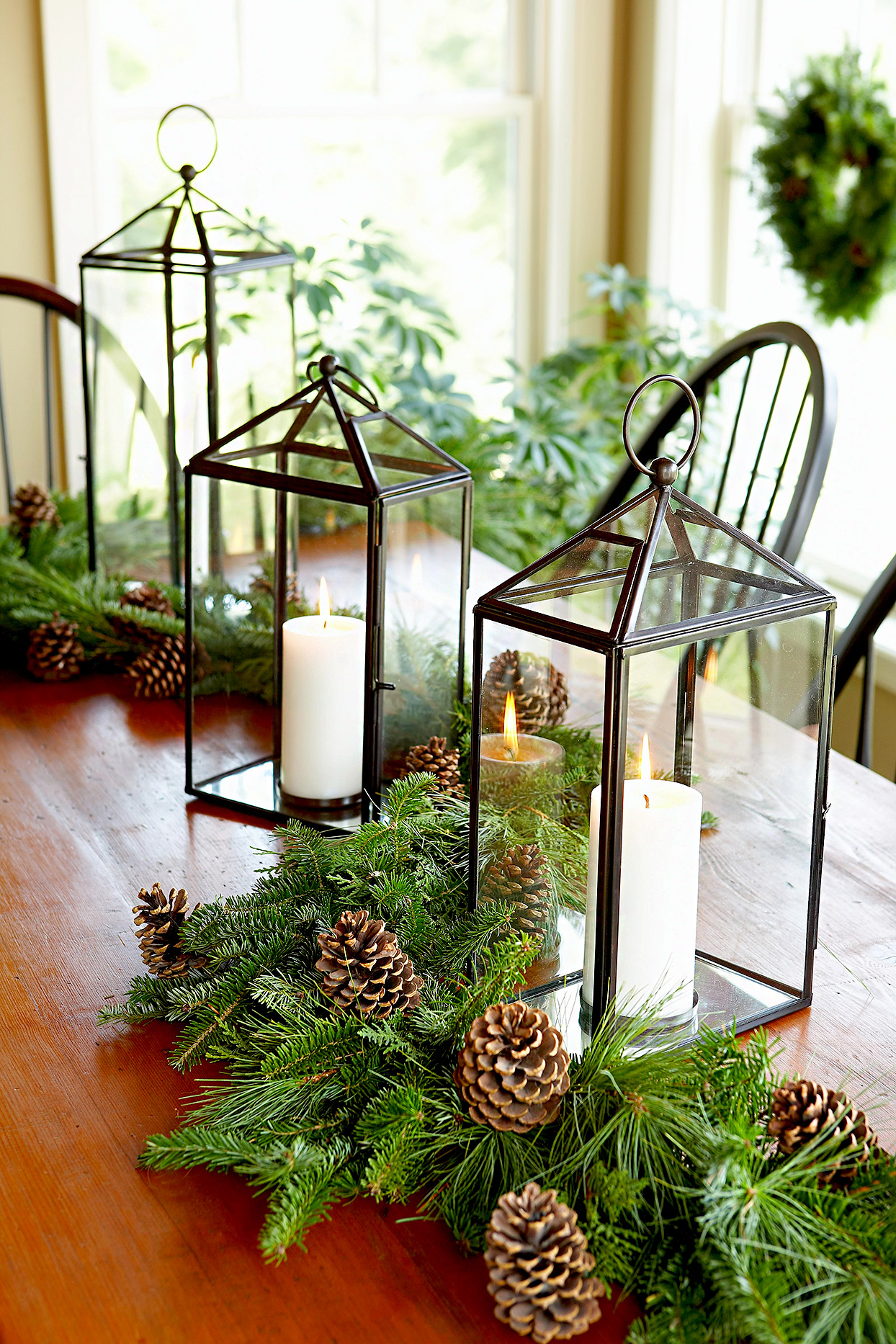 Table décor with candles, evergreens, and pinecones