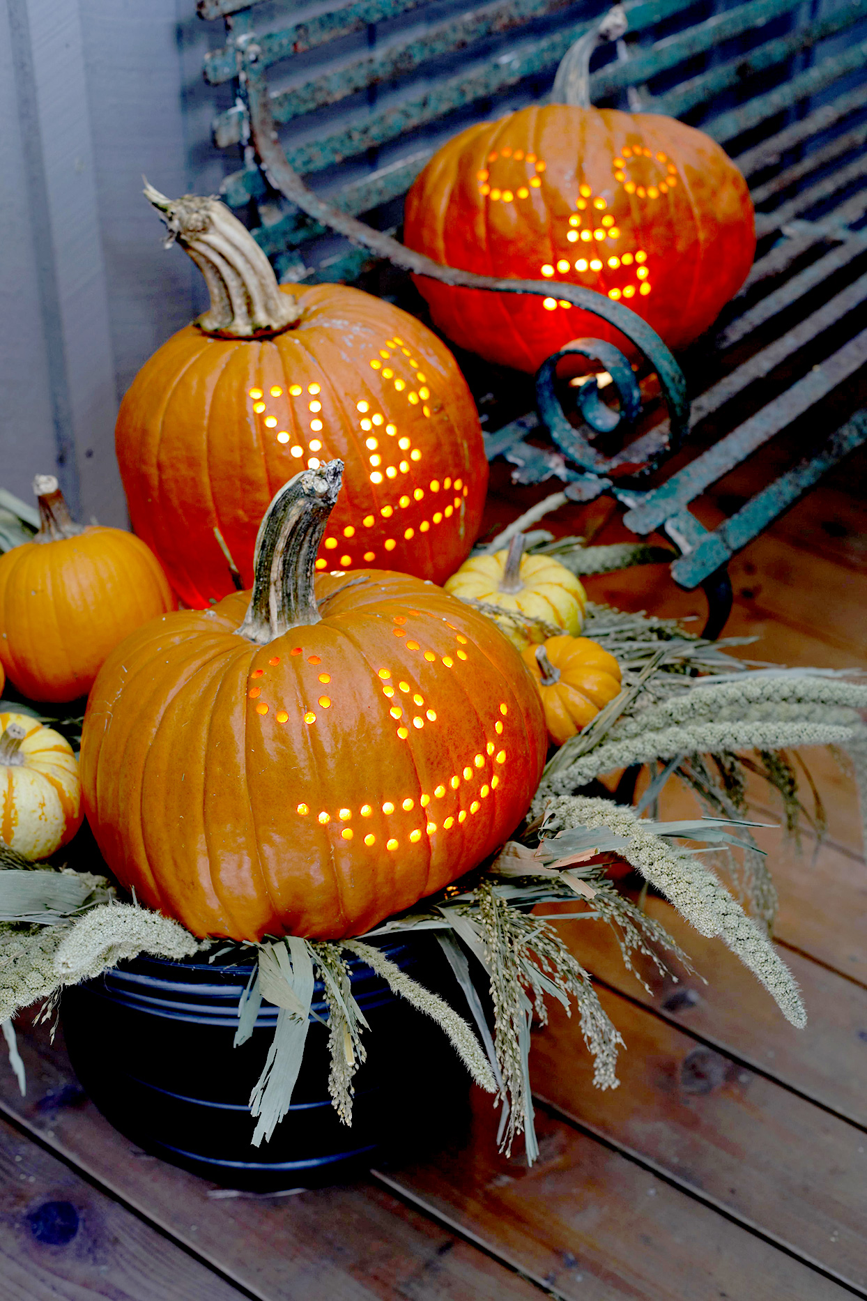 Three pumpkins carved with drill holes