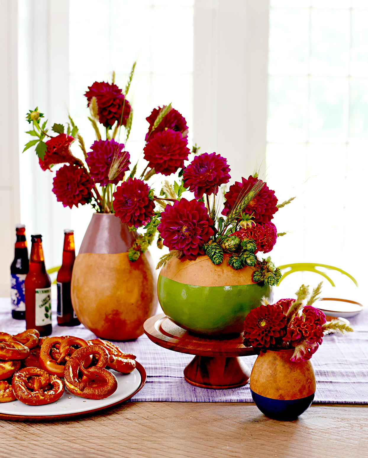 Three vases filled with burgundy flowers