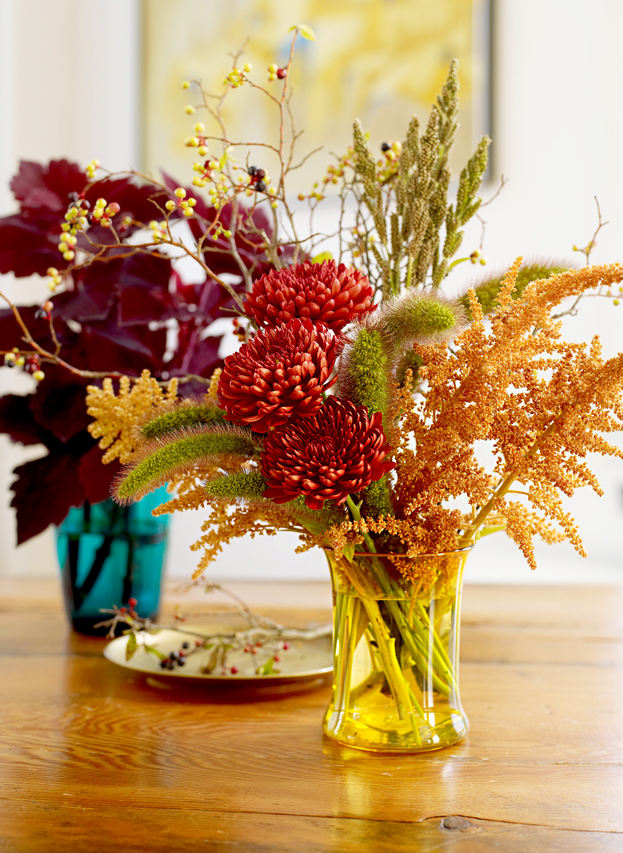 Two vases filled with fall colored plants