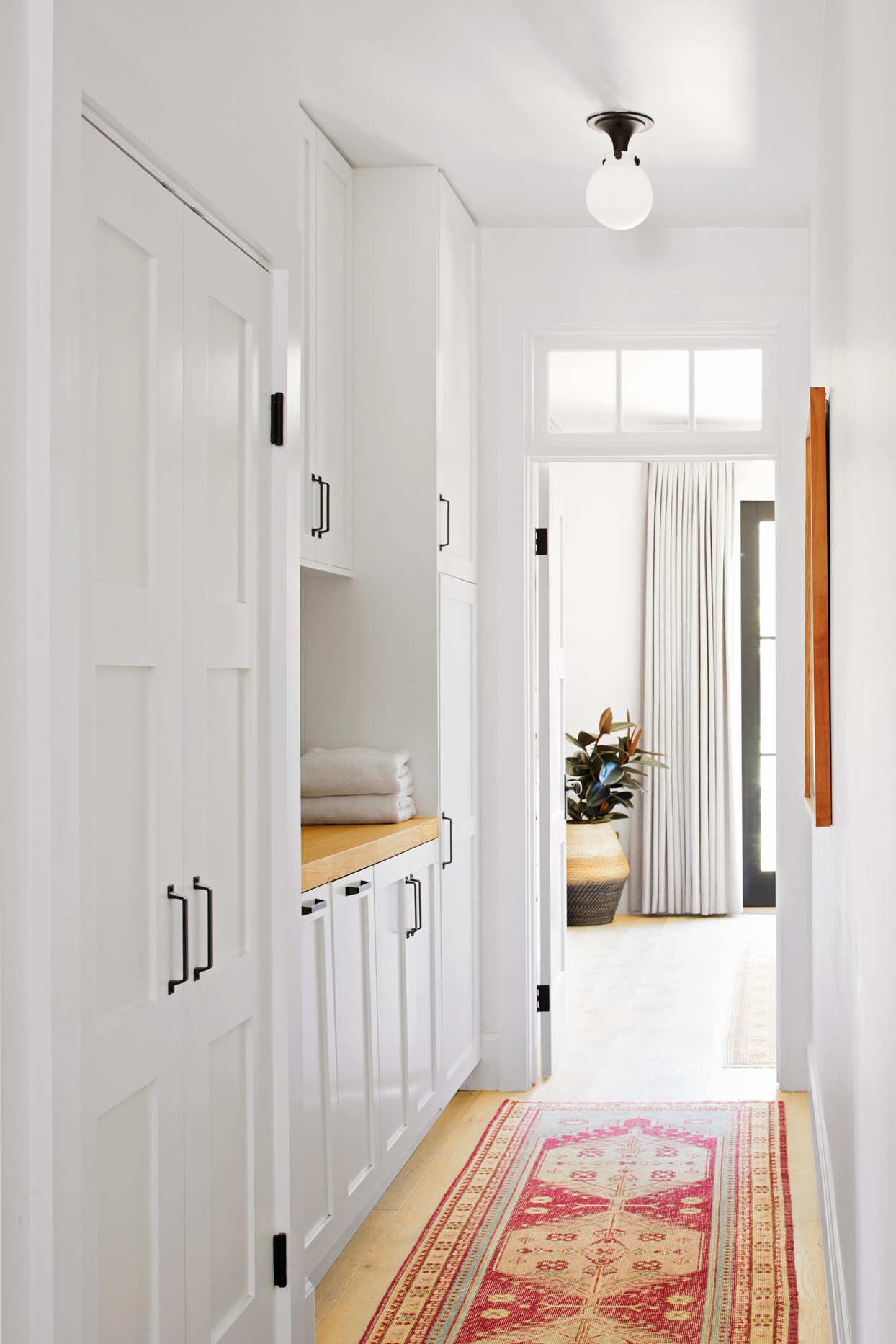 white cabinet hallway with red rug