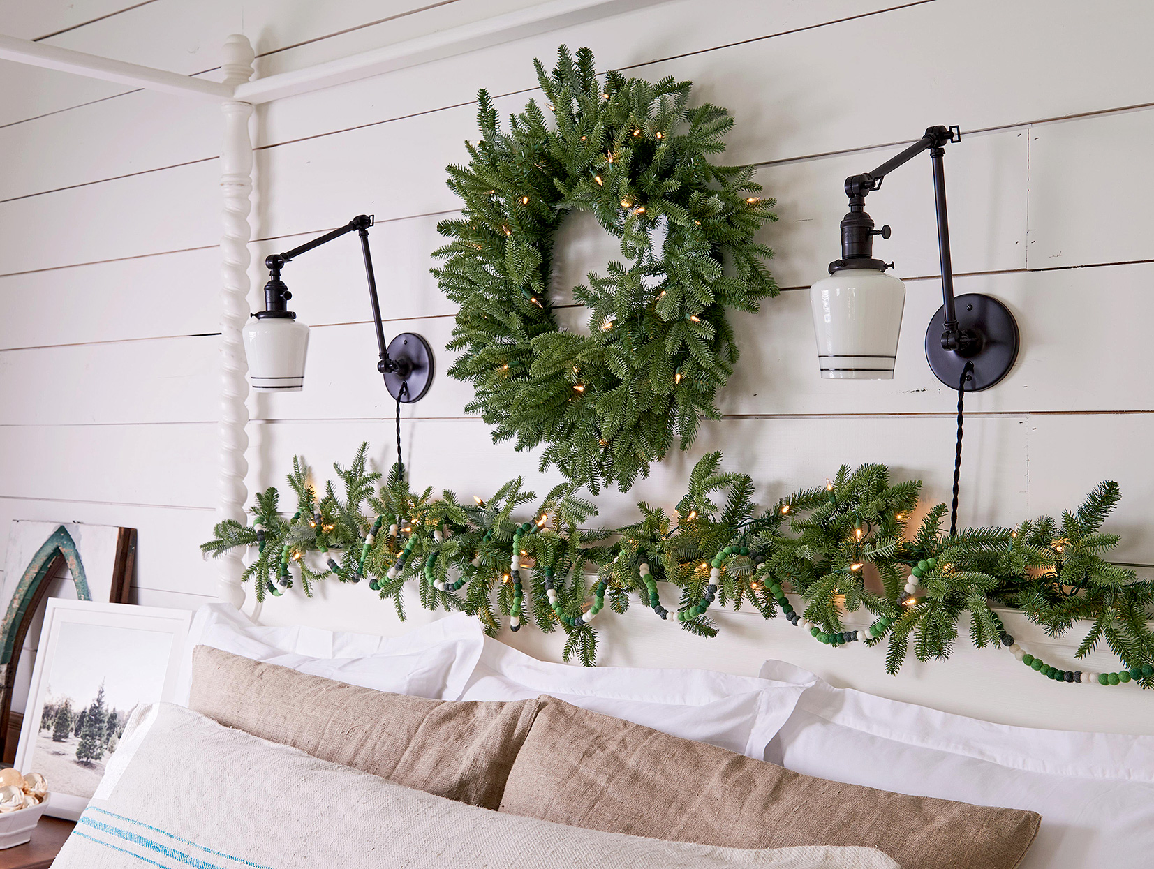 wreath, greenery and white lights above farmhouse poster bed