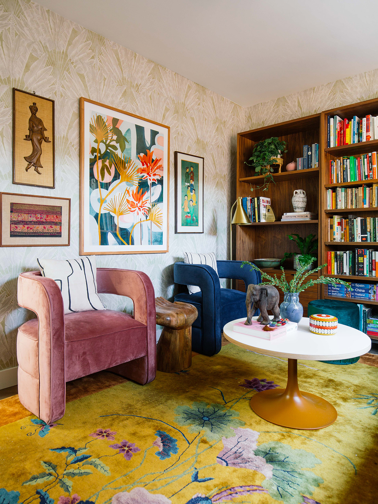 living room with pink and blue chairs bookcases and gallery wall of artwork