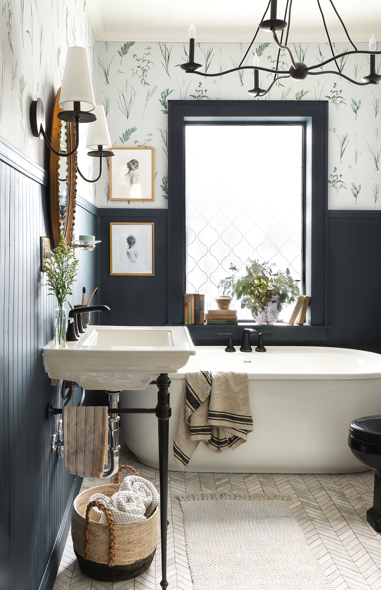 bathroom with pedestal sink bathtub and black wainscoting with botanical-patterned wallpaper above