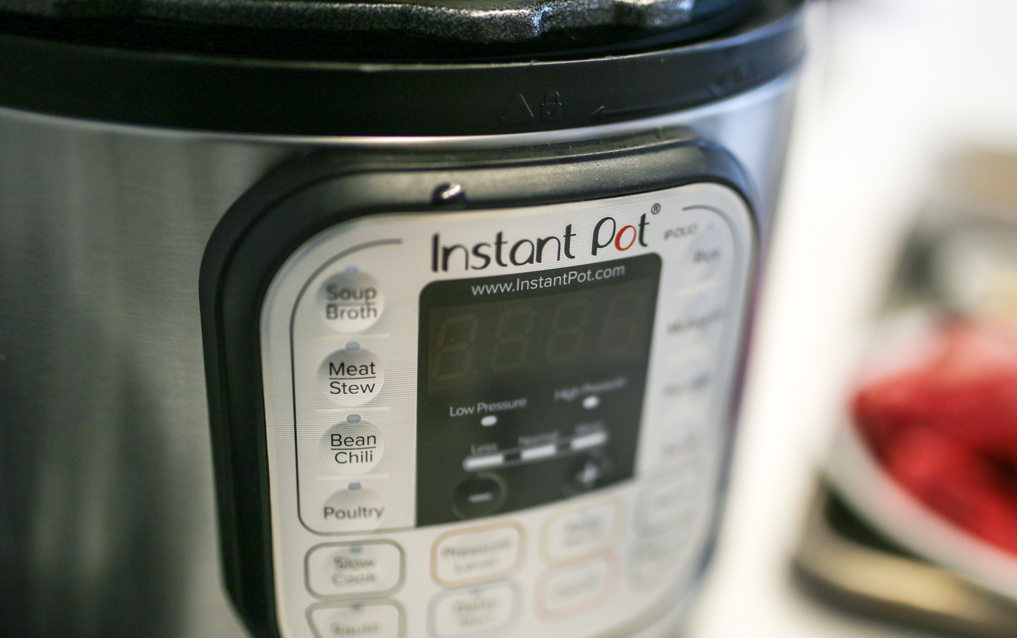 close up of an Instant Pot with blurry food in the background