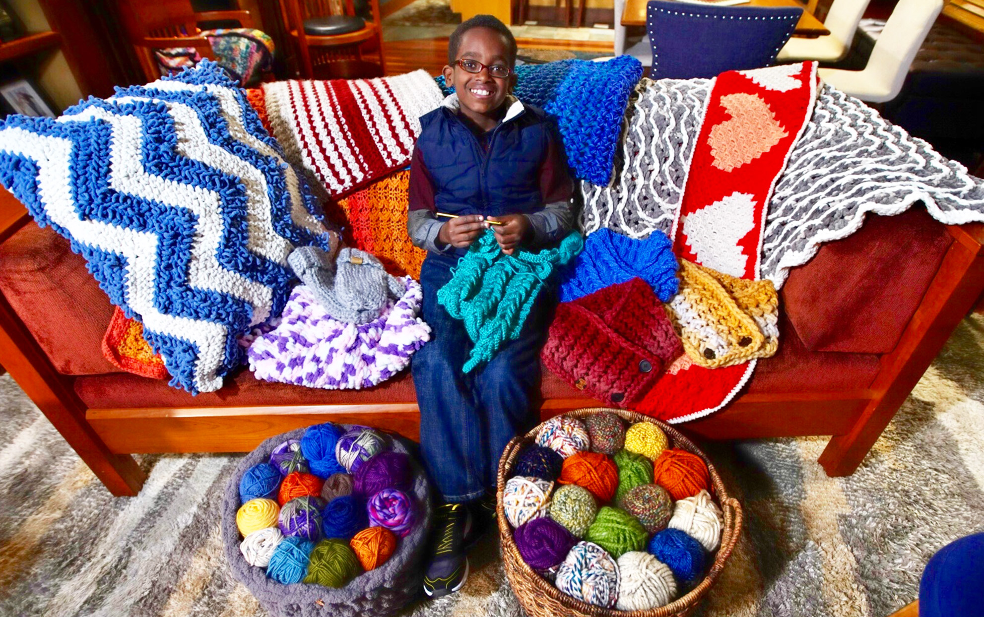 Jonah Larson sitting on a sofa knitting with knitting supplies nearby