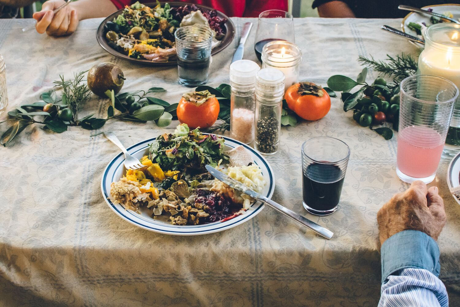 a thanksgiving table with plates of food and three peoples hands