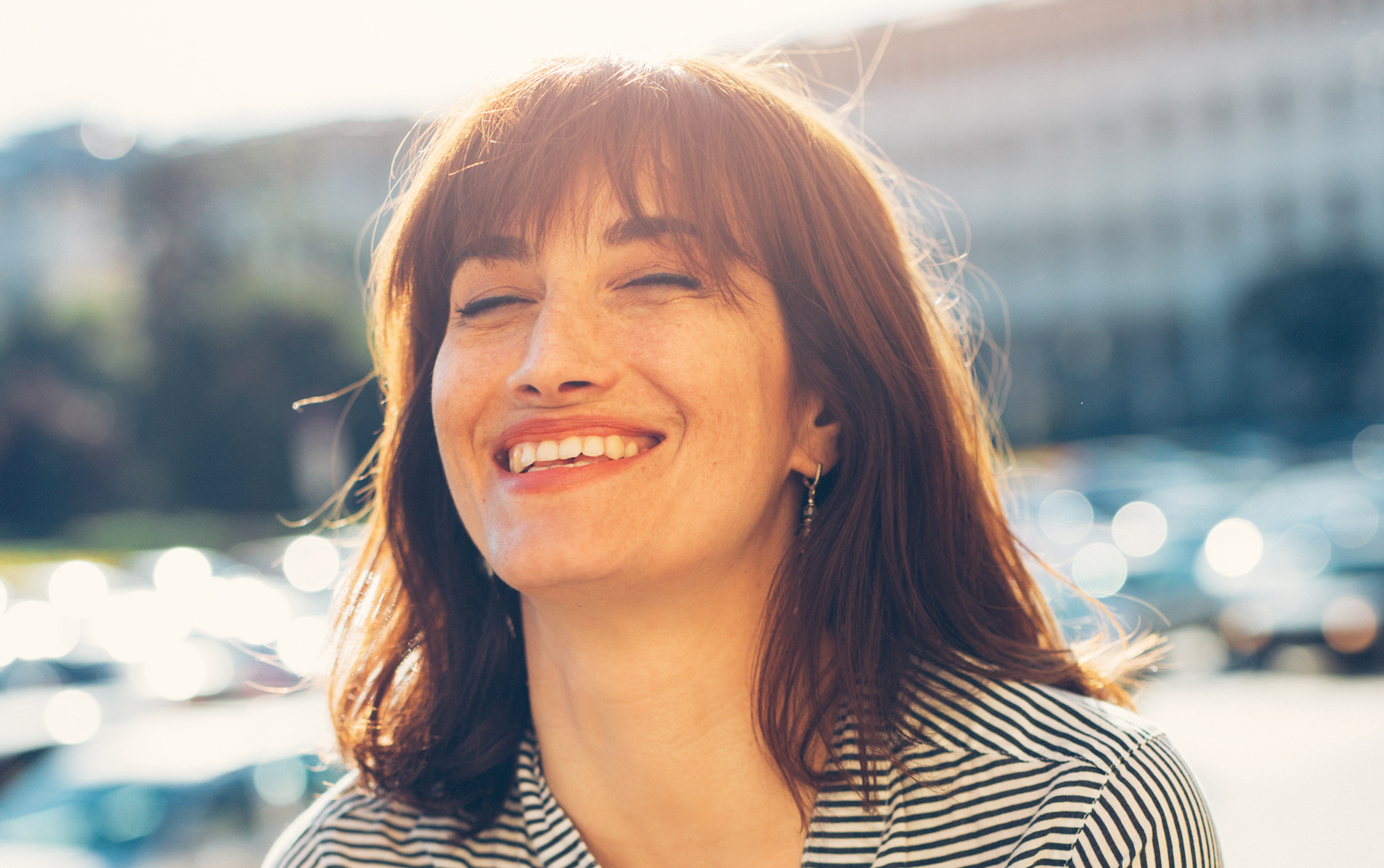 woman outside in the sunshine with brown long bob smiling in a striped shirt.