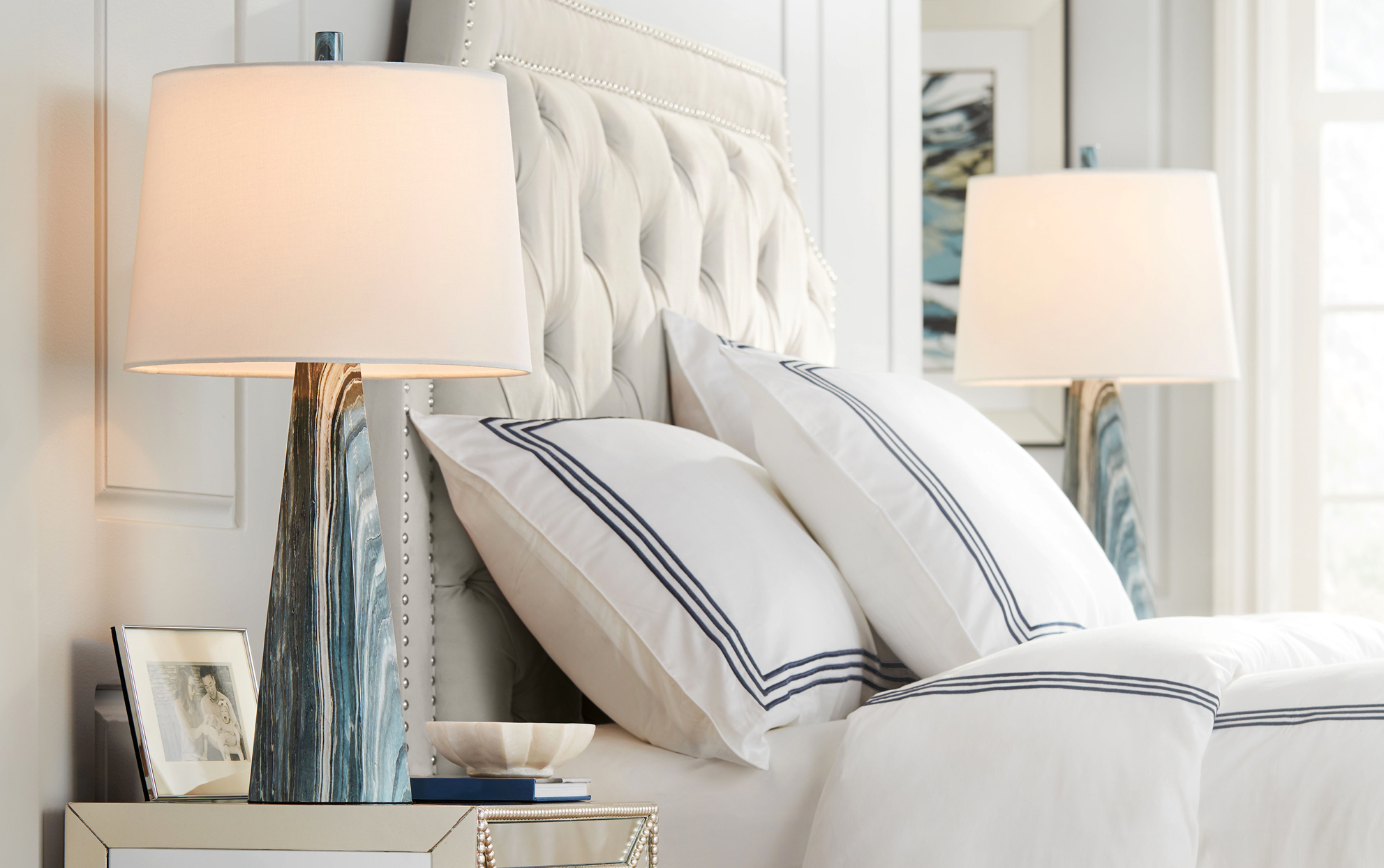 Bed and side tables with lamps in a white and cream palette