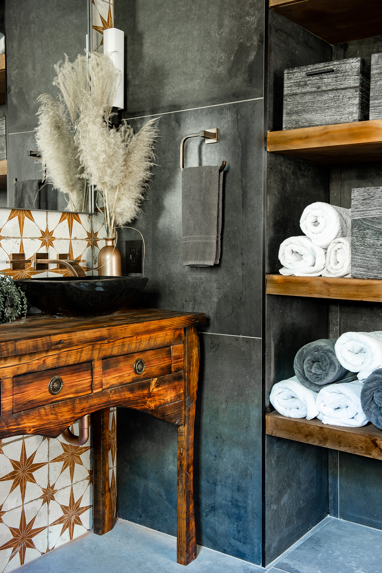 bathroom with slate tile floor and walls with wood vanity and builtin shelves lined with towels