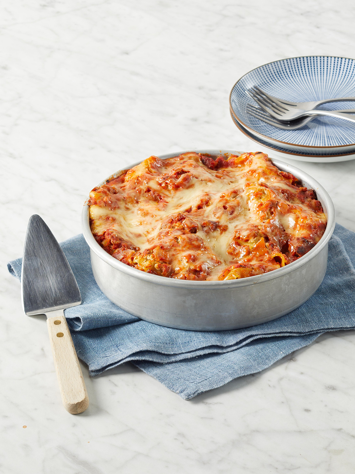 Instant-Pot Lasagna in an 8-inch cake pan on blue fabric with metal serving spatula