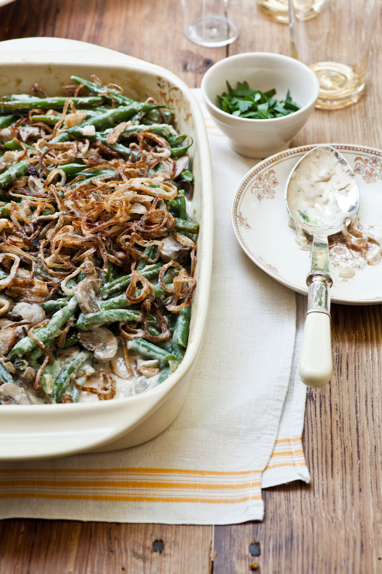 White pan of creamy green beans topped with crispy shallots