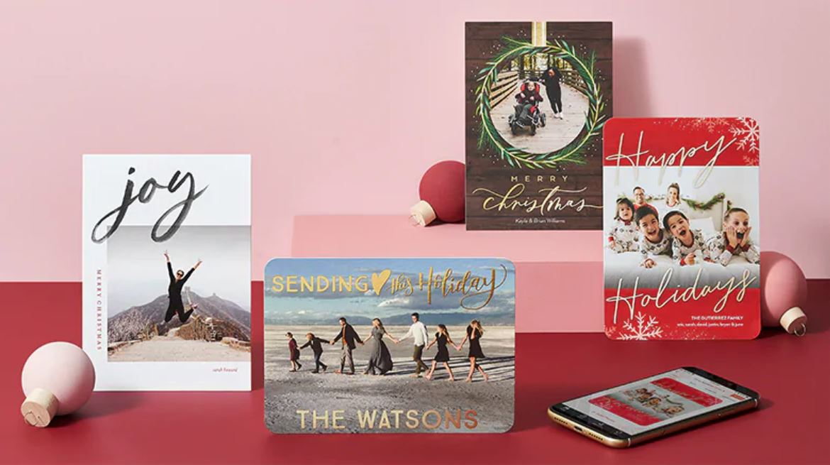 four holiday cards on a red and pink background