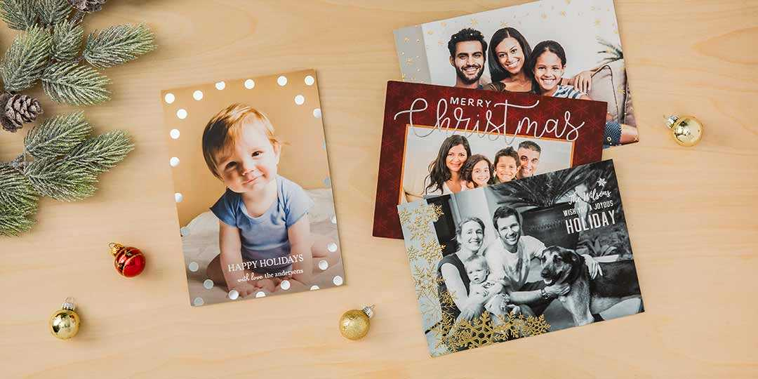 four christmas photo cards on a light tan wood background