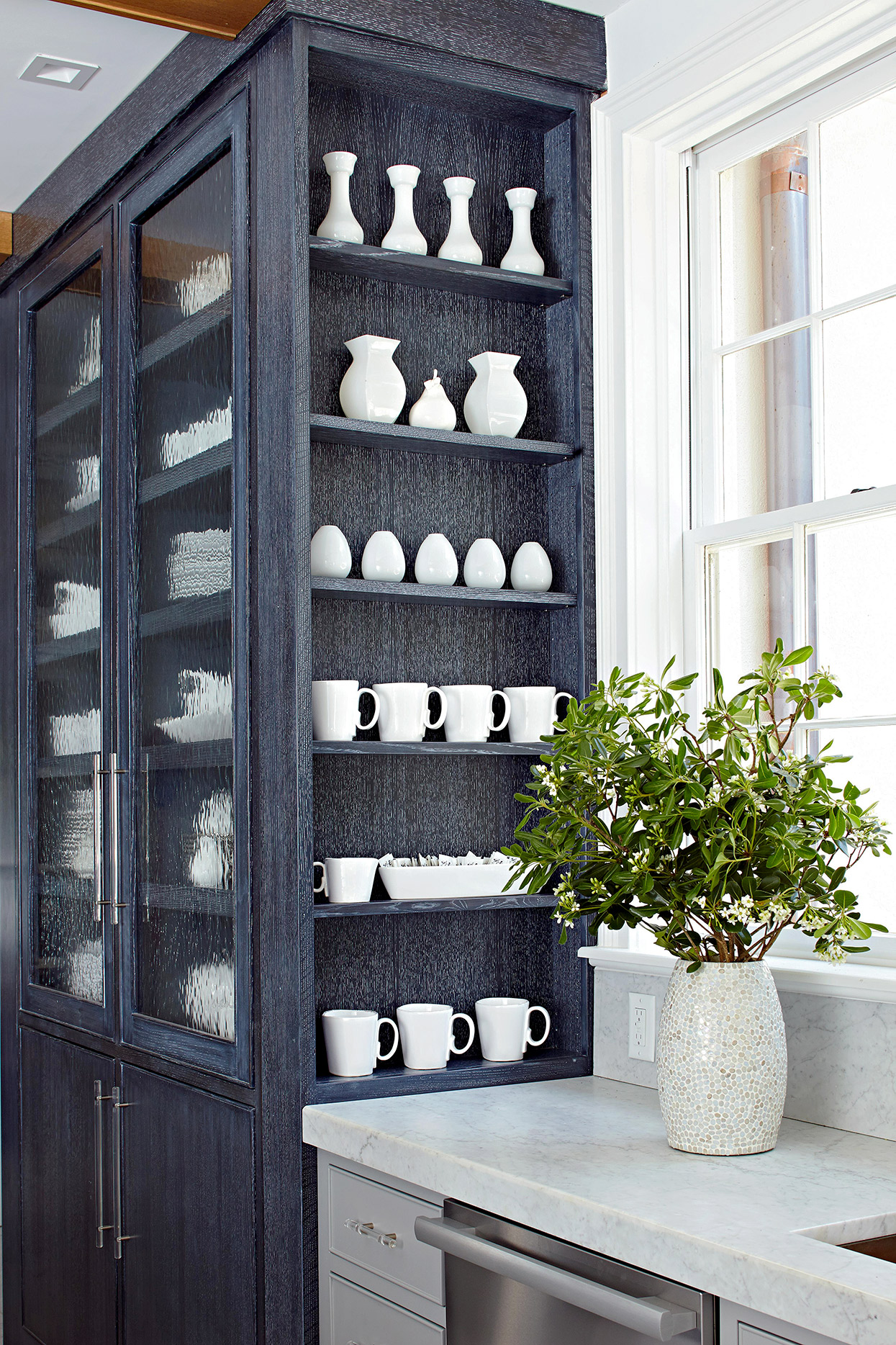 black cabinet in kitchen with shelves displaying uniform white dishes