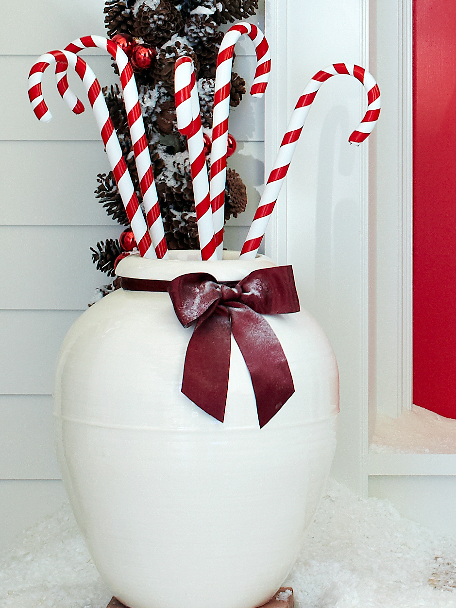 large white flower pot containing decorative candy canes