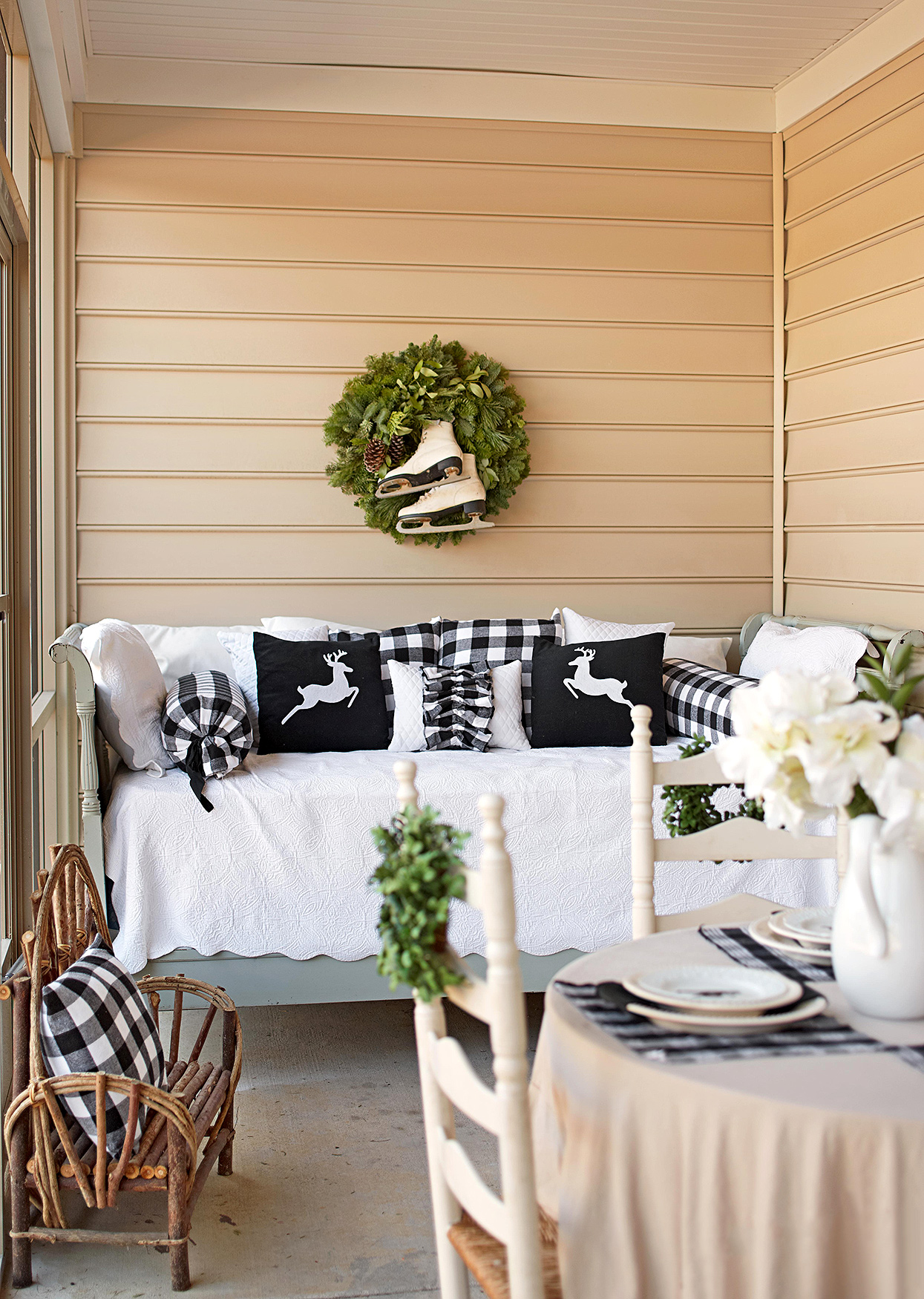 daybed with black and white winter linens underneath wreath with ice skates