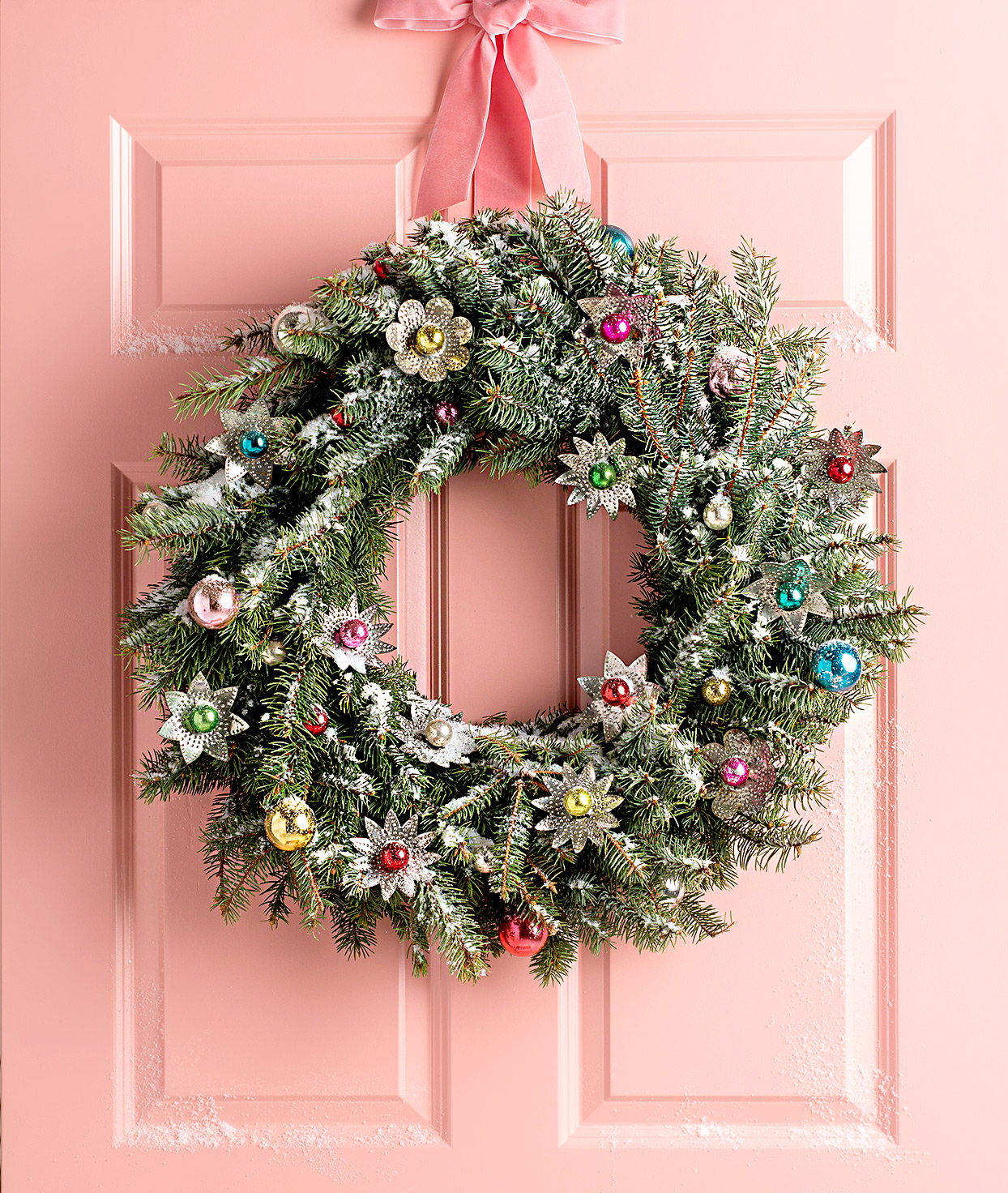 Door wreath with ornaments and pink bow