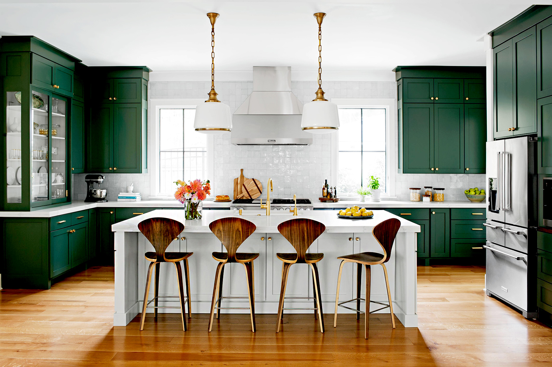 Kitchen with green cabinets and white island seating