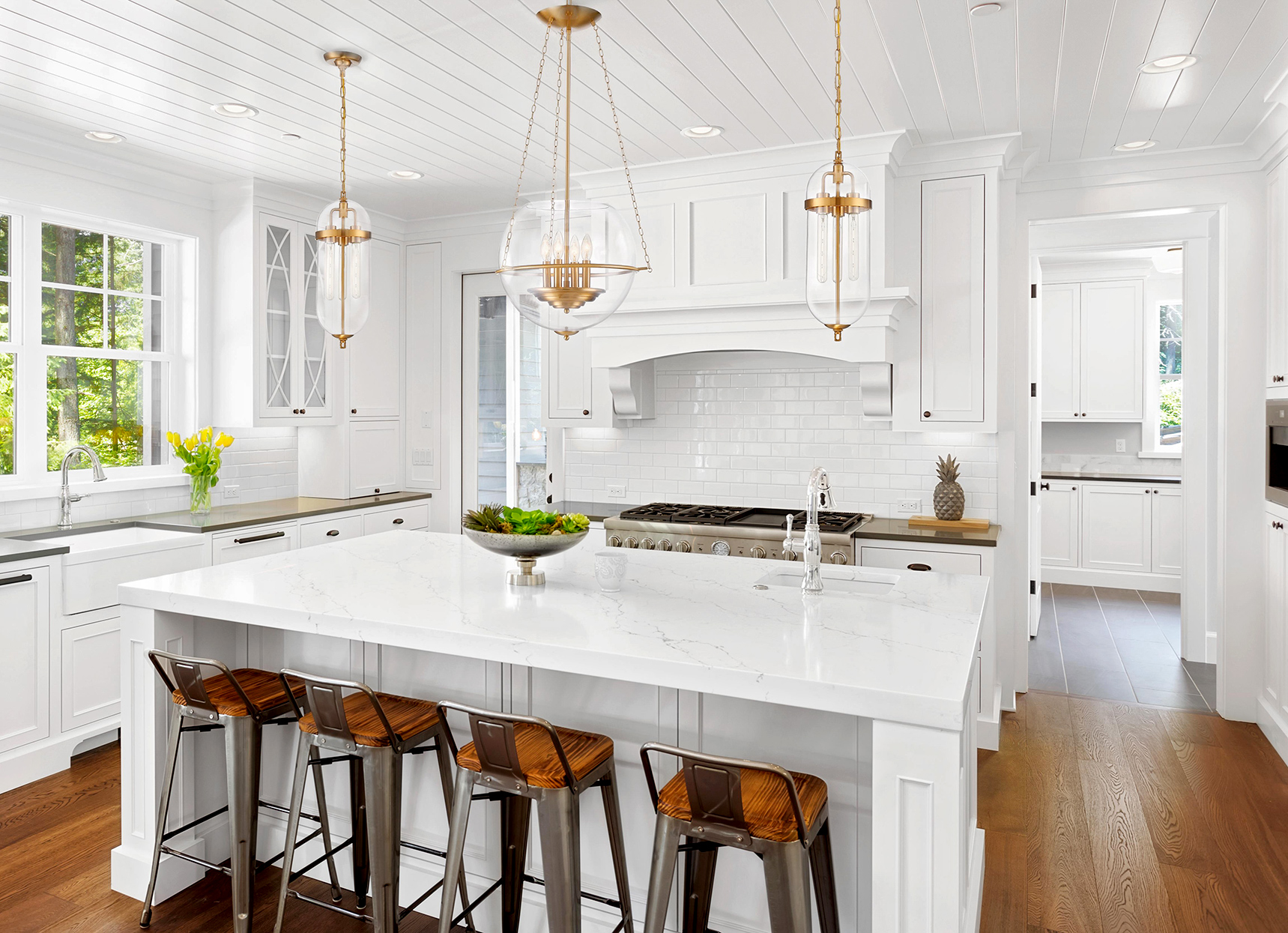 white kitchen with large island and glass pendant lights