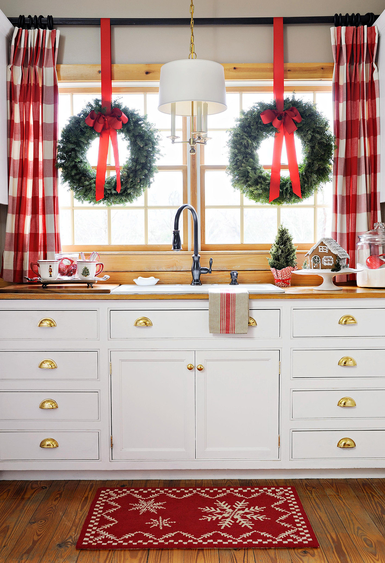 white kitchen sink with red plaid curtains and holiday wreaths in windows