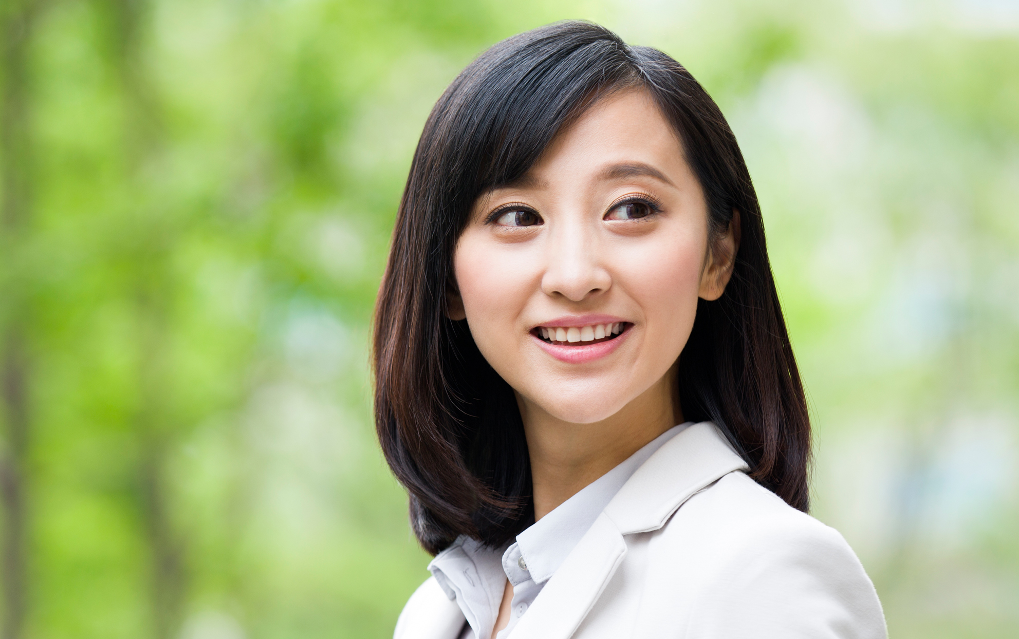 Asian woman with lob hairstyle smiling outside