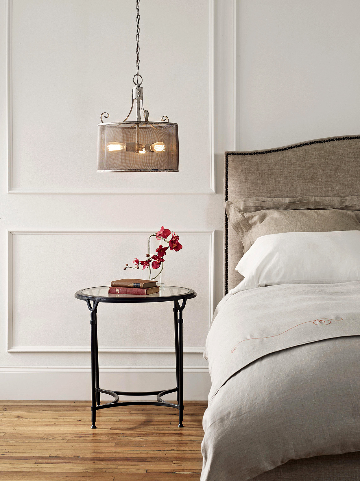 neutral bedroom with pendant light and wainscoting