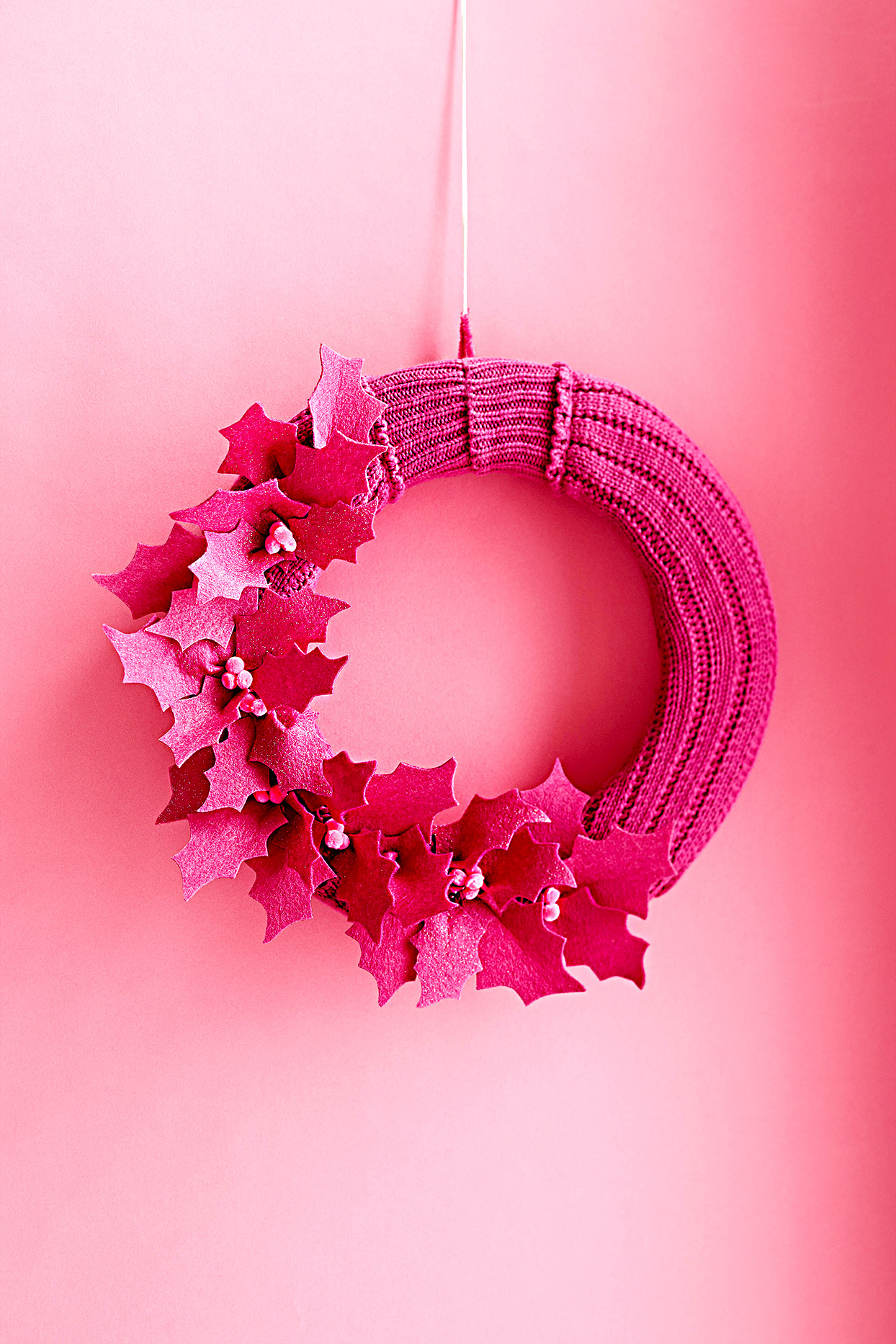 Pink wreath with holly leaves against pink wall