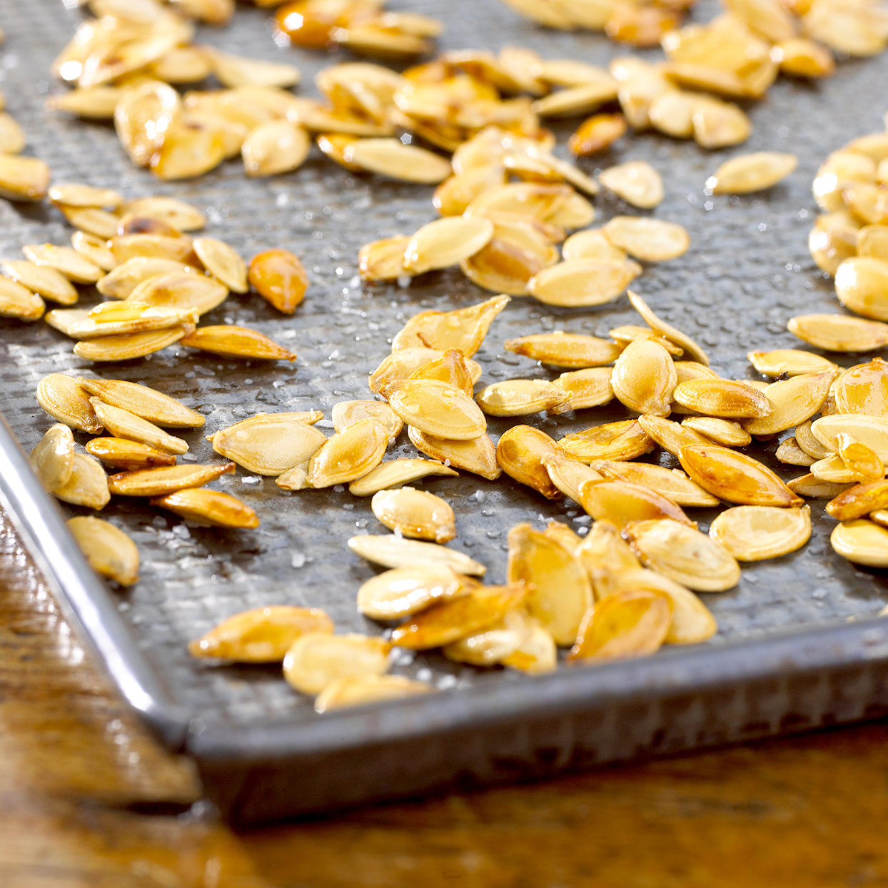 Roasted pumpkin seeds on cookie sheet