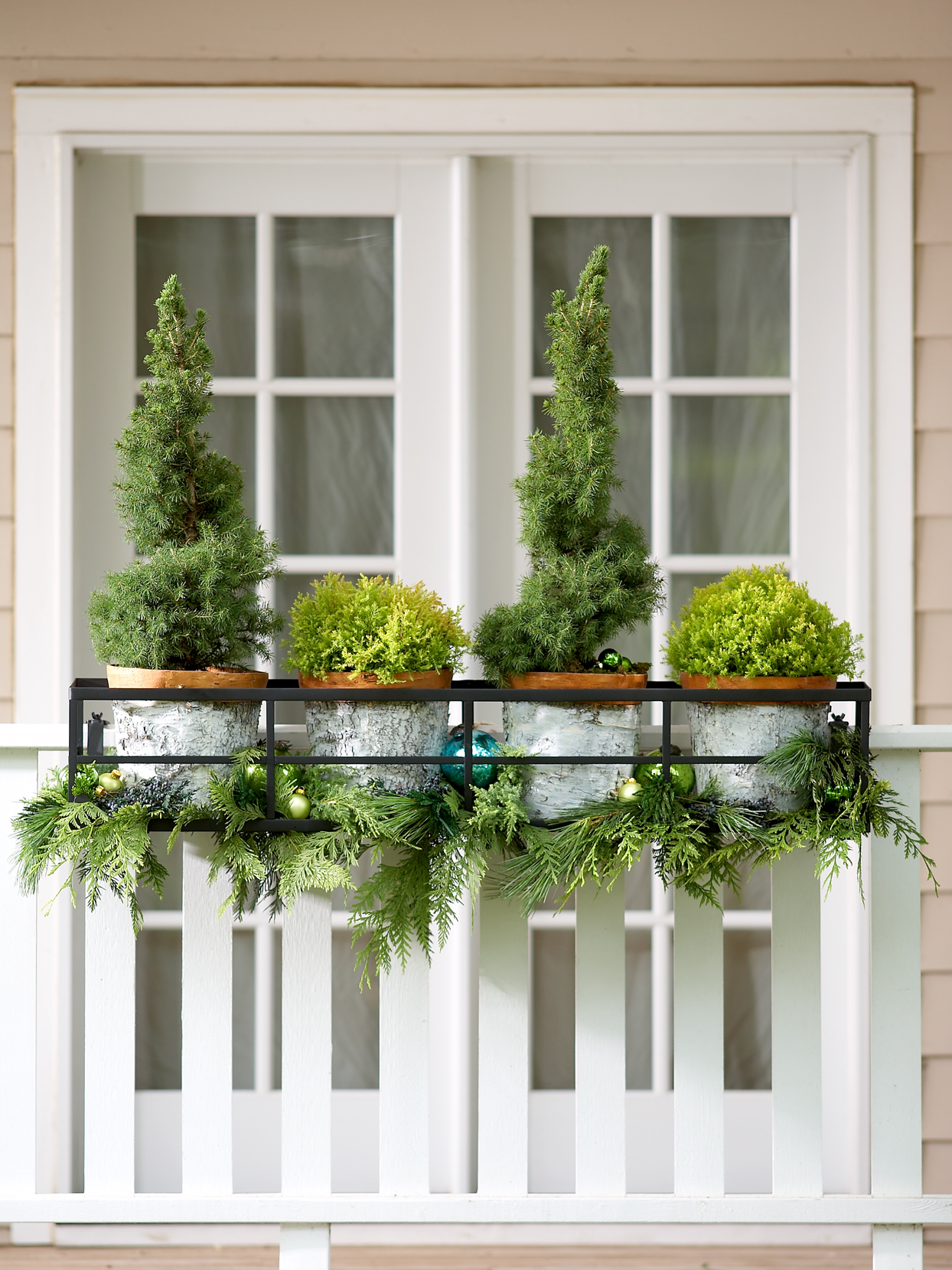 potted evergreens holiday decoration on porch railing