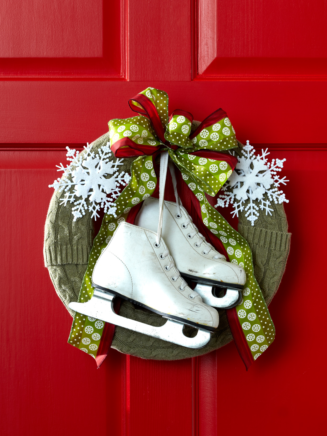 holiday wreath with ice skates hanging from a red door